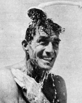 Jock in shower on beach.
