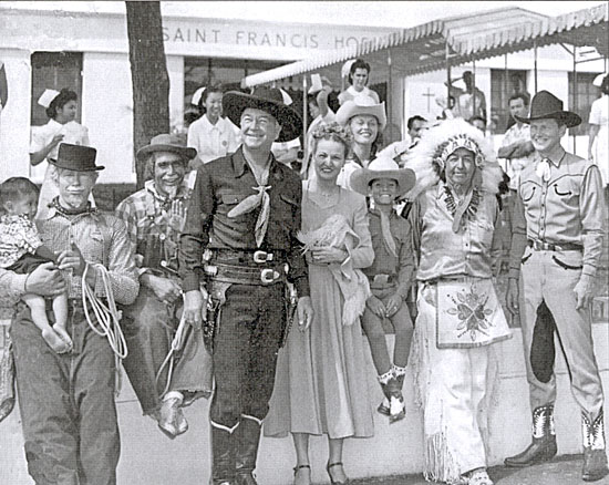 In 1948 Hopalong Cassidy took a Western show/rodeo to Honolulu, Hawaii. (Left-Right) Wilbur Plougher with a tiny St. Frances Hospital patient in his arms, Fess Reynolds (Don's father), Hoppy, unknown, Don Reynolds, stepmother Punkie (above Don), Chief White Eagle, and trick roper Carl Pitti.