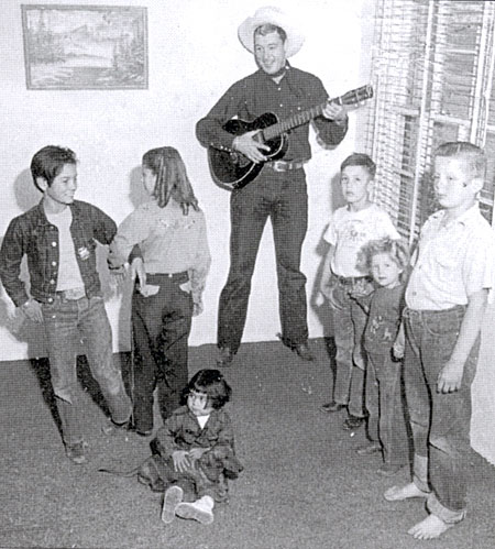 "Delores Randall and Don ""cut a rug"" as Jim (Red Ryder) Bannon provides the music while neighborhood kids look on circa 1949."