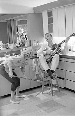 "Not sure what's going on here! Eric Fleming strums a guitar while Carol Byron sweeps the floor beneath him in a very domestic scene. Problem is, Fleming was never married, but Byron did make an episode of ""Rawhide"", ""The Woman Trap""."