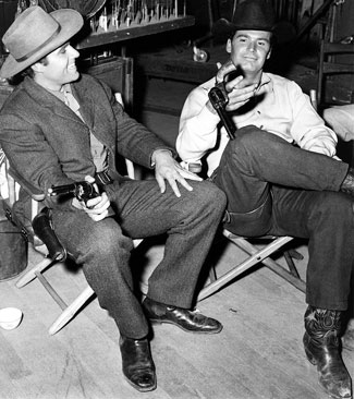 "Rex Reason and James Garner take a break from filming a ""Maverick""."