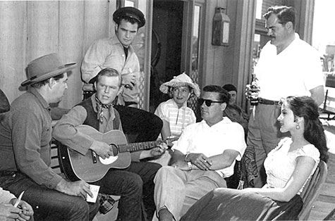 "Relaxing between scenes of TV's ""Riverboat"" are (L-R) John Mitchum, singer Rusty Richards, Burt Reynolds, woman (name unknown) choreographer for that episode of the series, director Dick Bartlett, scriptwriter Norm Jolley and guest star Debra Paget."
