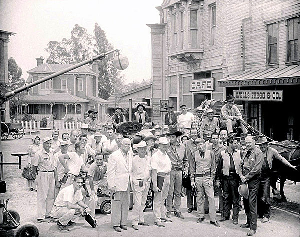 "Director Earl Bellamy (holding the script), Dale Robertson and the entire cast and crew of a ""Tales of Wells Fargo"" episode. Robertson's stunt double Dean Smith is mounted on the rear left."
