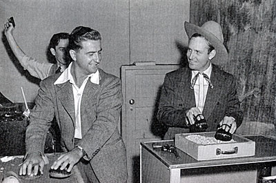 "Creating Gene Autry's radio show. A sound effects man uses the old reliable coconut shells to keep up with the hooves of Champion achieved by Gene himself. Note the door behind Gene which is used for everything from entering and exiting the front door of a cabin to entering and exiting Gene's office. Also note the turntable at the left for ""needle-drop"" sound effects and the other sound effects man holding a gun in the air."