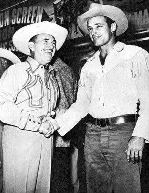 "Warner Bros. honcho Jack Warner congratulates Guy Madison on the success of ""Charge at Feather River"" and now the release of ""The Command""."