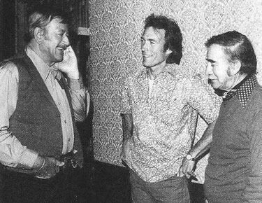 "Clint Eastwood and director Don Siegel visit with John Wayne on the  set of ""The Shootist""."