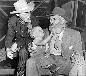 Roy Rogers smiles as his young son Dusty takes a tug at Gabby Hayes' beard.