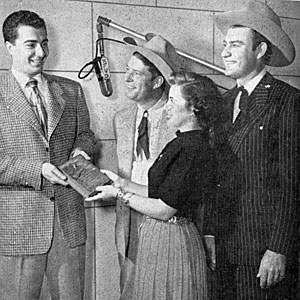 COUNTRY SONG ROUNDUP magazine columnist and KFVD Los Angeles radio DJ George Sanders accepts a gold plaque in 1950 from KFI-TV reporter Gloria Grant. The award, known as 'The Western Life', was presented every year by Tex Williams (right) and Smokey Rodgers to the person who has done the most to encourage western music in America.