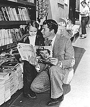 Audie Murphy shows a young fan an article about himself in a movie magazine.