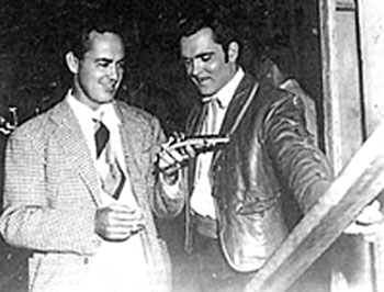 "Producer (and former actor) Buddy Rogers and star Richard Martin look over a prop gun used in their ""Adventures of Don Coyote"" ('47 Comet/UA)."