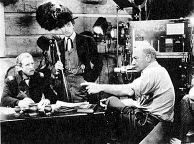 "For ""The Plainsman"" ('36) director Cecil B. DeMille gives direction to actors John Miljan as George Armstrong Custer and Gary Cooper as Wild Bill Hickok."