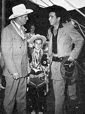 Gene Autry stopped off to meet Lash LaRue while both were appearing at an Illinois State Fair. Young fan in the middle is Roger Ladage of Vernon, IL.