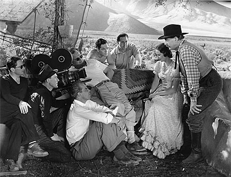 "Director Lesley Selander (white shirt seated on the ground) directs Evelyn Venable and Robert Barrat in a scene for Paramount's ""Heritage of the Desert"" ('39) while several crew members and star Donald Woods (center) look on."