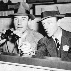 Randolph Scott and Fred Astaire share a box and a pair of field glasses at Santa Anita Turf Club in 1938.