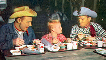 "Young Deever Jenkins gets a treat lunching with Pat Brady and Roy during the making of a June 1955 ""Roy Rogers Show"" TV episode."