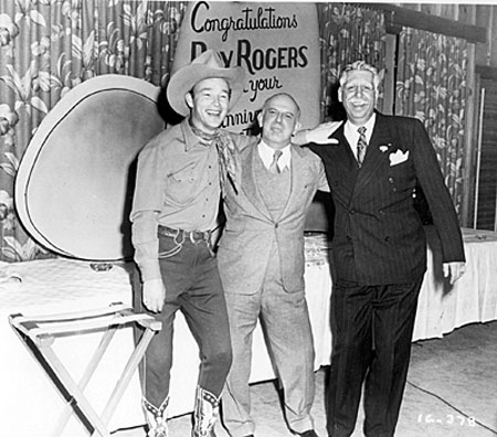 Roy, Republic President Herbert J. Yates and Roy's business manager Art Rush celebrate Roy's ninth year at Republic in 1947.