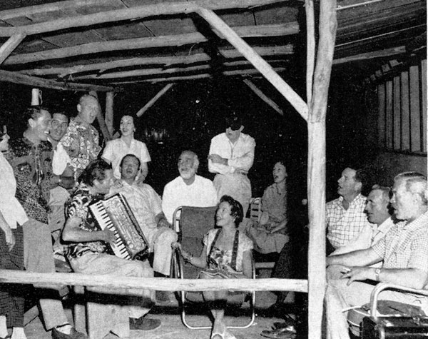 Time to relax and sing. From left, standing: Mrs. Ken Curtis, Ken Curtis, Jeffrey Hunter, Harry Carey Jr., Mrs. Wayne, John Ford (eye patch). Seated, L-R): Dan Borzage, John Wayne, Antonio Moreno, Mrs. C. V. Whitney, Dorothy Jordan, C. V. Whitney, Winton Hoch, Ward Bond.