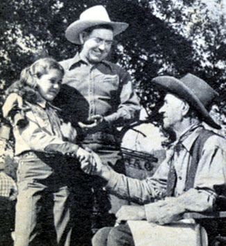 "Johnny Mack Brown introduces his daughter, 12 year old Cynthia, to Milburn Morante, Johnny's co-star in ""Outlaw Gold"" ('50 Monogram)."