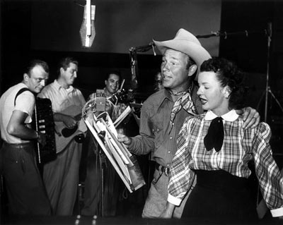 Roy Rogers and Dale Evans recording a song together in 1955.
