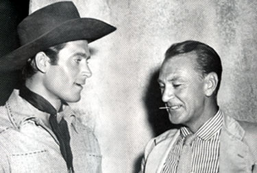 "Clint ""Cheyenne"" Walker and Gary Cooper meet for a chat on the Warner Bros. back lot."