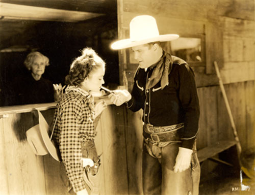 "Ken Maynard lights up for leading lady Lona Andre between scenes of ""Trailing Trouble"" ('37 Grand National)."
