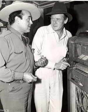 "Leo Carrillo and Charles Bickford find a little diversion with a jukebox inbetween scenes for Universal's ""Riders of Death Valley"" serial ('41) filmed around Mojave, California."