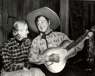 "Leo Carrillo serenades Jeanne Kelly in this off-stage shot during the making of ""Riders of Death Valley"" ('41)."