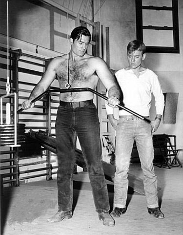 "Will (""Sugarfoot"") Hutchins watches as Clint (""Cheyenne"") Walker works out in the Warner Bros. gym."