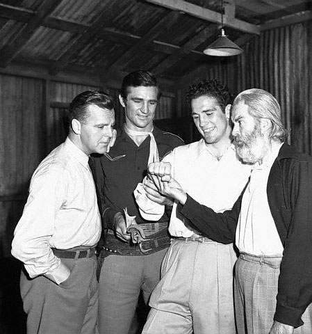 "Light Heavyweight boxing champion Billy Conn, known as The Pittburgh Kid, lets Neil Hamilton, Sammy Baugh and Gabby Hayes take a look as his strong right hand during the making of the Republic serial ""King of the Texas Rangers"" in July 1941."