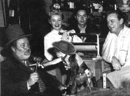 "Monkeying around on the ""Judge Roy Bean"" set during the filming of the ""Citizen Romeo"" episode regarding a organ grinder's monkey are (L-R) Edgar Buchanan as Judge Roy Bean, Jackie Loughery as Letty Bean, Jack Beutel as Jeff Taggard and producer Russell Hayden (who often played Texas Ranger Steve)."