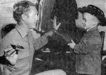 "Five year old Randy Cooper of Albuquerque covers Steve McQueen of ""Wanted Dead or Alive"" with McQueen's own ""mare's laig"" (a cut down version of a Model 92 Winchester 44-40 rifle). McQueen was appearing at the New Mexico State Fair in October 1959."