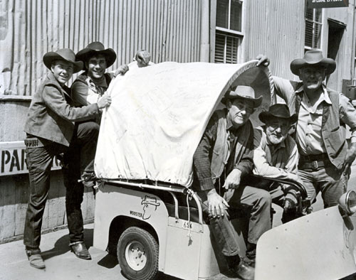 "The later cast of ""Wagon Train"" gather around Frank McGrath's Wooster-Wagon on the Universal back lot. (L-R) Michael Burns, Robert Fuller, John McIntire, Frank McGrath (as Charlie Wooster) and Terry Wilson. You probably can't read them in this photo but the wagon tarp is covered with autographs."