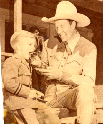 Bill Elliott takes time to feed a bite of cake to a young boy (at some sort of military school judging by the uniform?) in 1941.