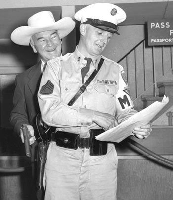 William Boyd (Hopalong Cassidy) arrives at the Rhein-Main Airport in Frankfort, Germany, August 27, 1954, to begin a European vacation with his wife Grace. For a publicity photo, Hoppy appears to be playfully swiping the M.P.'s weapon. (Thanx to Joel O'Brien.)