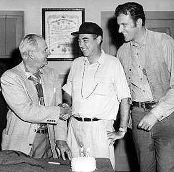 "Meeting for the first episode of ""Gunsmoke: Matt Gets It"" in 1955 are (L-R) 1st assistant director Glenn Cooke, writer/producer/director Charles Marquis Warren and James Arness."