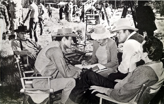 "Dan Blocker, Gilbert Roland and the script supervisor discuss a scene for ""Bonanza: The Lonely Runner"" (10/10/65) as Kelly Thorsden (L) and Pat Conway (R-back to camera) listen intently."