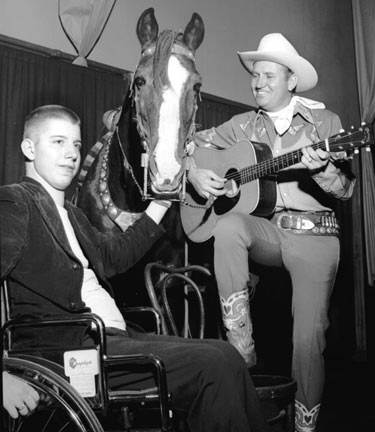 In a wheelchair, sixteen year old Ben Jarrett of Lexington, TN, visits Gene Autry during his appearance in Memphis, TN, on November 23, 1952. Gene first met Jarrett two years prior when the boy was flat on his back paralyzed from the waist down after he was injured diving into a shallow stream. (Thanx to Ray Nielsen.)
