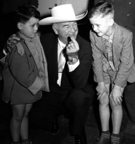 William Boyd, Hopalong Cassidy, presents Hoppy coins to a couple of young fans as he and his wife Grace arrived at the Rhein-Main Airport in Frankfurt, Germany, on August 27, 1954, during the European segment of their around-the-world vacation. (Thanx to Joel O'Brien.)