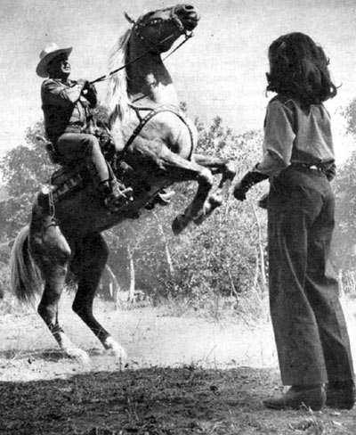 Johnny Mack Brown's daughter Cynthia watches her dad rear his palomino Rebel in November 1949. Cynthia was 12.