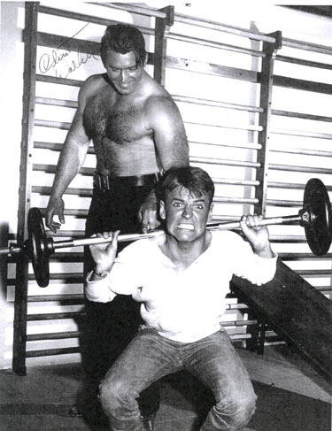 "Will ""Sugarfoot"" Hutchins and Clint ""Cheyenne"" Walker working out in the Warner Bros. gym circa 1960. Will captioned this photo for us, ""I'm tryin' to raise your spirits."""