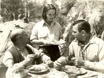 "Harvey Clark, Louise Brooks and Buck Jones have a bite to eat on the set of Universal's ""Empty Saddles"" (1936)."