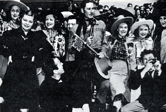 "(L-R) Lola Lane (with hat), Mayo Methot, Humphrey Bogart (sitting), Claire Windsor, Frank McHugh (behind Flynn), Rosemary and Priscilla Lane, John Garfield (with camera) and Jean Parker join Errol Flynn in accepting the key to the city of Dodge City, Kansas during the November 1938 premiere of Warner Bros.' ""Dodge City""."