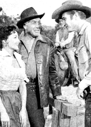 "Mari Blanchard and Cesar Romero talk with Eric Fleming during a break from the filming of ""Rawhide: Incident of the Stalking Death"" in November 1959. Note Paul ""Wishbone"" Brinegar on horseback in the background."