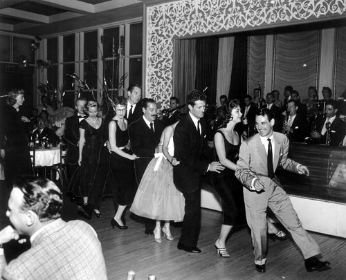 "Ray Anthony leads a group as they dance to his big hit of ""The Bunny Hop"" at Ciro's. Behind Anthony is actress Mitzi Gaynor and Hugh O'Brian. Man with the mustache is comedian Jerry Colonna. Marie Windsor watches on the left."