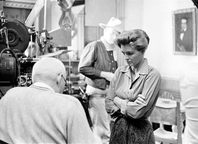 "Angie Dickinson discusses her ""Rio Bravo"" script with director Howard Hawks. Note in the first photo John Wayne is mostly obscured by the camera, but by the second photo he has walked into the background."