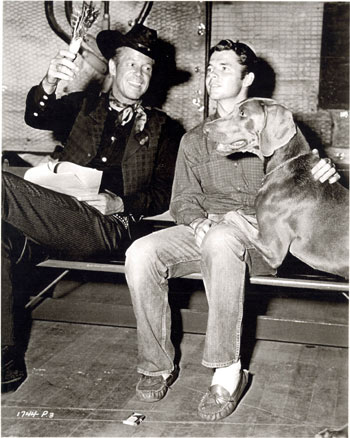 "Audie Murphy and Dan Duryea try to rehearse their lines but are interrupted by Audie's dog Long John, a gift from and names for John Huston, on the set of ""Ride Clear of Diablo"" ('53 Universal-International)."