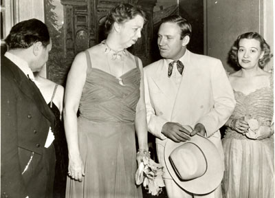 "Eleanor Roosevelt and Gene Autry in a photo taken January 30, 1940, during a week in Washington, D.C., celebrating President Roosevelt's 58th birthday. (Is that Edward G. Robinson on the left?) Other celebrities invited to Washington for the ten day celebration included Olivia de Havilland, Mickey Rooney and Tyrone Power. Gene's January 28 ""Melody Ranch"" broadcast originated from the Press Club auditorium where he was joined by Eleanor in a patriotic tribute. (Thanx to Neil Summers.)"