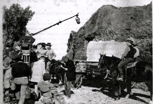 "Filming a ""Wagon Train"" episode in the Conejo Valley west of Los Angeles. Robert Horton and Ward Bond can be seen left of the rock formation. Frank McGrath leans against the wagon. (Thanx to Terry Cutts.)"