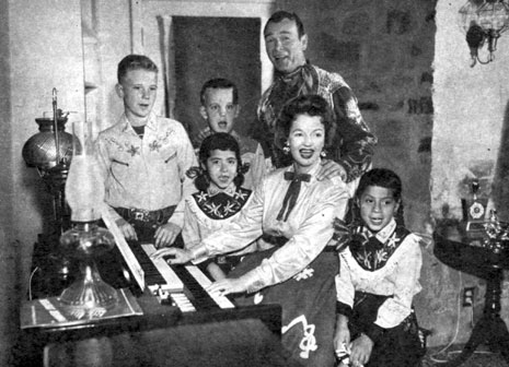 "Roy Rogers and Dale Evans and four of their children sing Christmas Carols at their home in Chatsworth, CA. (L-R) Roy ""Dusty"" Rogers Jr., Sandy, Debbie and Dodie."