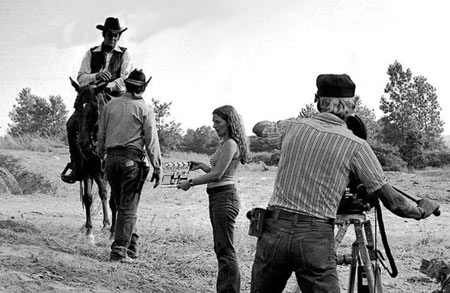 "Cameraman Darrell Cathcart sets up for a scene with Sunset Carson in ""Marshal of Windy Hollow"". Kathy Patton is holding the clapboard and Jerry Whittington walks toward Sunset."